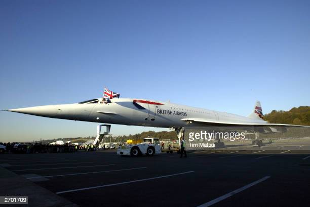 British Airways Concorde passenger jet is towed on the rampway, while pilot Cpt. Mike Bannister waves a British flag November 5, 2003 at Boeing Field...