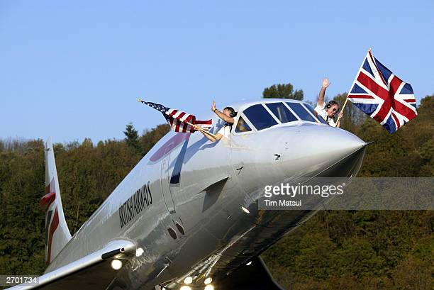 British Airways Concorde passenger jet is towed on the rampway while copilot Cpt Les Brodie and pilot Cpt Mike Bannister wave flags November 5 2003...