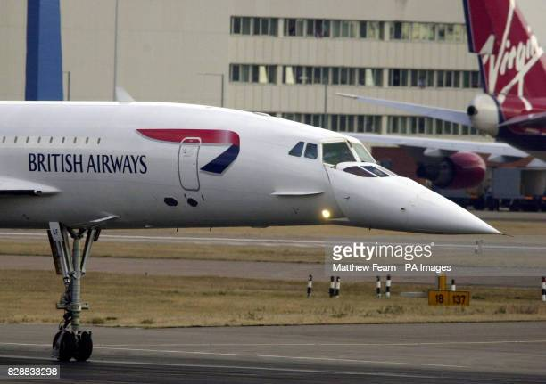 A British Airways Concorde passes a Virgin tail fin before takeoff at Heathrow Airport Concorde will be flying their final commercial flight today as...