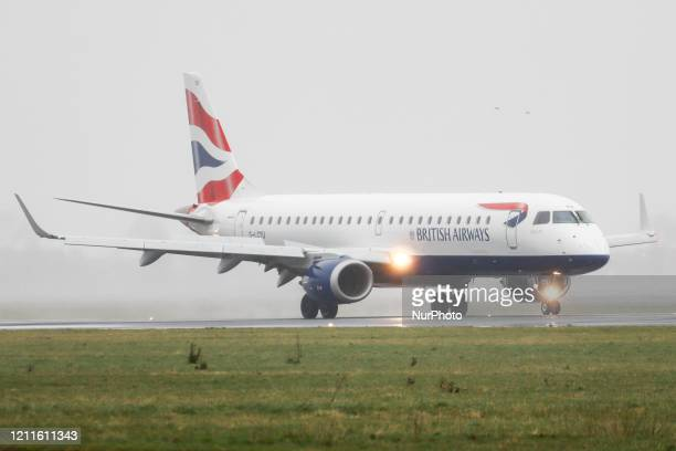 A British Airways Embraer ERJ190 commercial aircraft as seen landing and taxiing in bad weather with fog and rain at the runway of Amsterdam Schiphol...