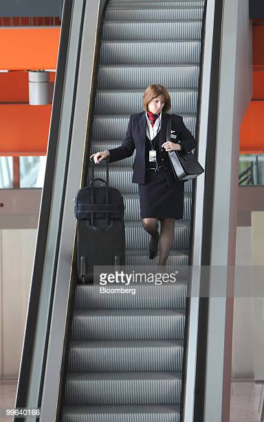 A British Airways employee uses the escalator in Terminal 5 at Heathrow airport in London UK on Monday May 17 2010 British Airways Plc and the Unite...