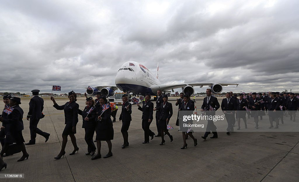 British Airways (BA) flight crews wave British Union flags as the company's new Airbus A380 aircraft arrives at Heathrow airport in London, U.K., on Thursday, July 4, 2013. British Airways will start regular services with the Airbus SAS A380 superjumbo a week earlier than planned after taking delivery of the first of 12 of the doubledeckers today. Photographer: Chris Ratcliffe/Bloomberg via Getty Images
