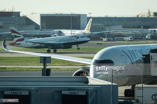 British Airways flight takes off as a Virgin Atlantic aeroplane waits at terminal 3 of Heathrow Airport on March 16, 2020 in London, England. As the...