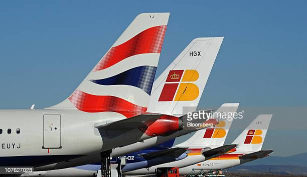 British Airways left and Iberia Lineas Aereas de Espana SA logos are seen on aircraft tailfins at Barajas airport in Madrid Spain on Thursday Dec 16...