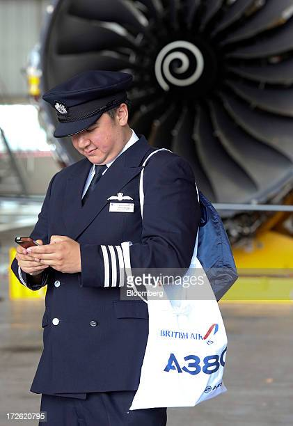 A British Airways pilot carries an A380 branded bag as he uses a mobile device near an aircraft engine in the company's hangar at Heathrow airport in...