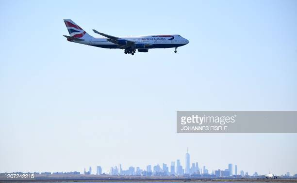A British Airways plane coming from London Heathrow is seen above the skyline of Manhattan before it lands at JFK airport on March 15 2020 in New...