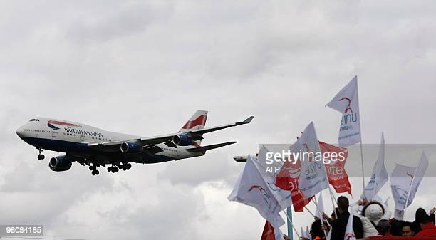 A British Airways plane flies near striking British Airways cabin crew members at Heathrow Airport at the start of a fourday strike on March 27 the...