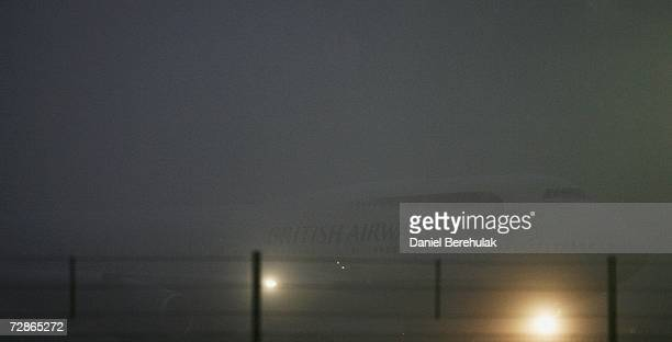 British Airways plane is seen through dense fog as it prepares to take off at Heathrow Airport on December 21 2006 in London England A heavy cover of...