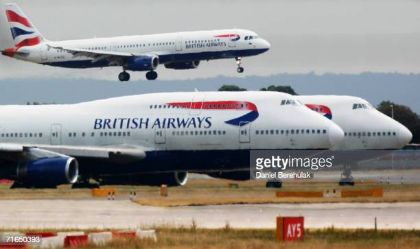British Airways plane lands as two other grounded planes sit on the runway at Heathrow Airport Terminal one on August 10 2006 in London England...