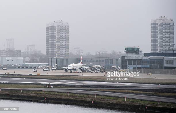 British Airways plane sits beside the runway at London City Airport as security personnel patrol the tarmac as flights are delayed due to fog on...