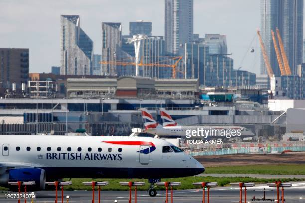British Airways plane taxis at the London City Airport, in east London, on March 16, 2020. - IAG, the owner of British Airways and Spanish carrier...