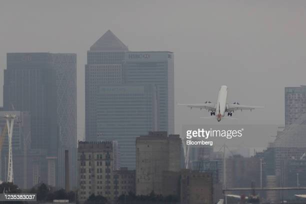 British Airways Plc passenger aircraft takes off from London City Airport in view of the Canary Wharf financial district in London, U.K., on Monday,...