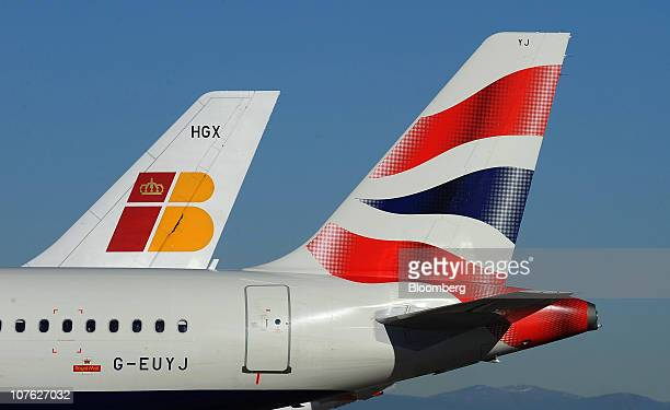 British Airways Plc right and Iberia Lineas Aereas de Espana SA logos are seen on aircraft tailfins at Barajas airport in Madrid Spain on Thursday...