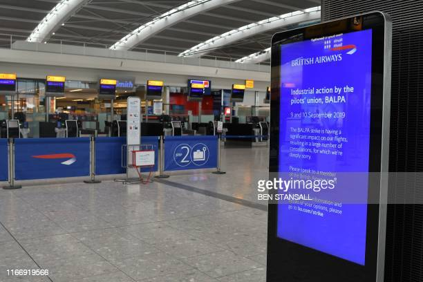 A British Airways sign displays information on industrial actionn in the neardeserted departure area at Heathrow airport Terminal 5 in west London on...