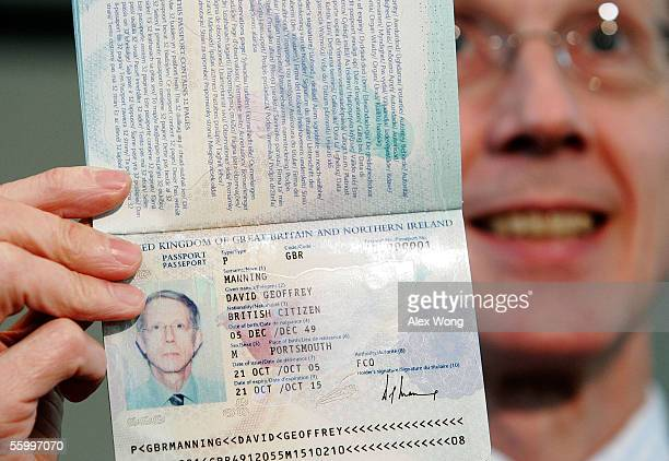 British Ambassador to the United States Sir David Manning shows reporters the inside pages of a new British biometric European Union passport which...