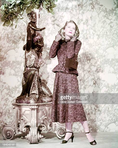 British American actress Joan Fontaine standing next to a statue circa 1940 She is wearing a suit and headscarf