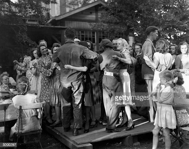 British and American soldiers dancing with German girls in a Berlin street cafe only days after the fraternisation ban was lifted at the end of World...
