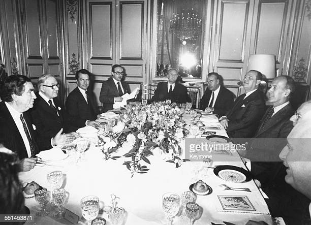 British and French politicians discussing foreign relations around a dinner table, including British Prime Minister James Callaghan and French...