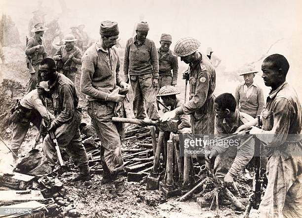 British and Indian officers and troops inspecting Japanese weapons including a gelignite bomb captured by the men of the 3rd Battalion of the 10th...