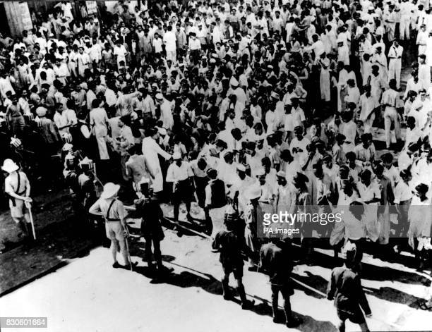 British and Indian police officers, armed with lathis, holding back the crowd during rioting in Bombay, capital of the Bombay Presidency. A few...