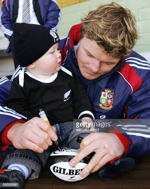 British and Irish Lions captain Brian O'Driscoll signs a ball for tenmonth old All Black fan William Hodge at Stratford as the Lions prepares for...