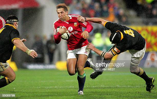 British and Irish Lions centre Gavin Henson fends off the tackle of Wellington lock Luke Andrews and prepares to take on prop Joe McDonnell during...