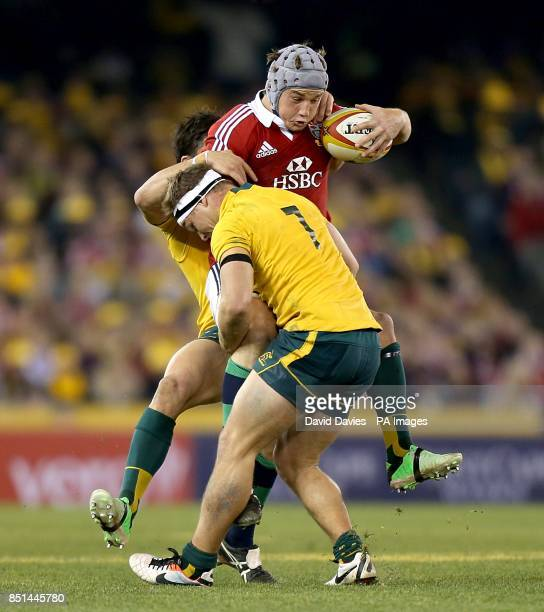 British and Irish Lions' Jonathan Davies is challenged by Australia's Michael Hooper and Adam AshleyCooper