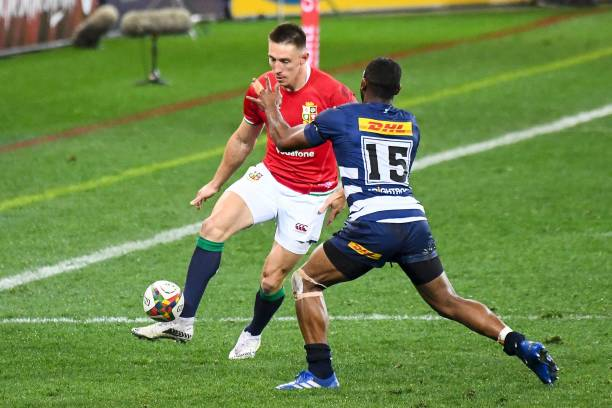British and Irish Lions' wing Josh Adams (L) kicks the ball past Stormers full-back Sergeal Petersen during the rugby union tour match between Stormers and the British and Irish Lions at The Cape Town Stadium in Cape Town on July 17, 2021. (Photo by RODGER BOSCH / AFP) (Photo by RODGER BOSCH/AFP via Getty Images)