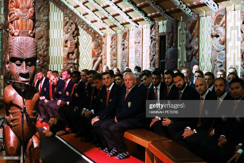 British and Lions rugby head coach Warren Gatland (C) and the rest of the team listen to speeches in the meeting house during a Maori welcoming at Waitangi Treaty Grounds in Waitangi on June 4, 2017. / AFP PHOTO / POOL / Hannah Peters