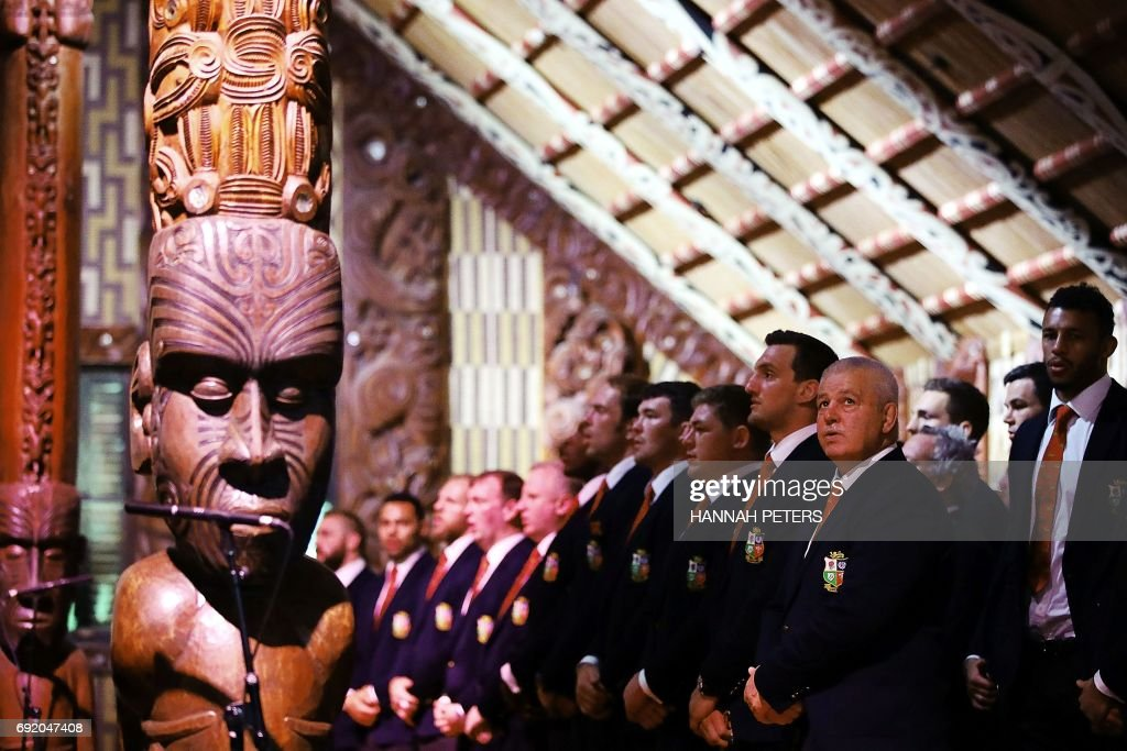 British and Lions rugby head coach Warren Gatland (2nd R) sings with the rest of the team in the meeting house during a Maori welcoming at Waitangi Treaty Grounds in Waitangi on June 4, 2017. / AFP PHOTO / POOL / Hannah Peters