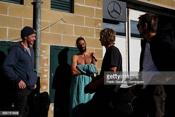 British Andrew Cotton and Portuguese Hugo Vau surfers chat with friends after their big waves session on December 17 2016 in Nazare Portugal Nazare's...