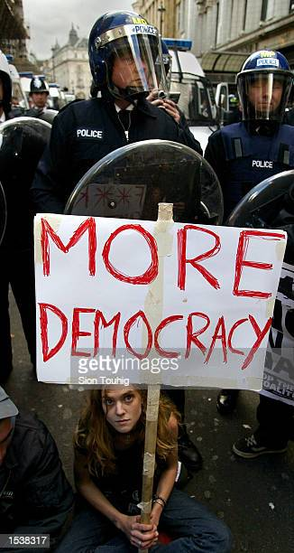 British anticapitalist protester holds a banner in front of riot police at a May Day demonstration May 1 2002 in London There were sporadic clashes...