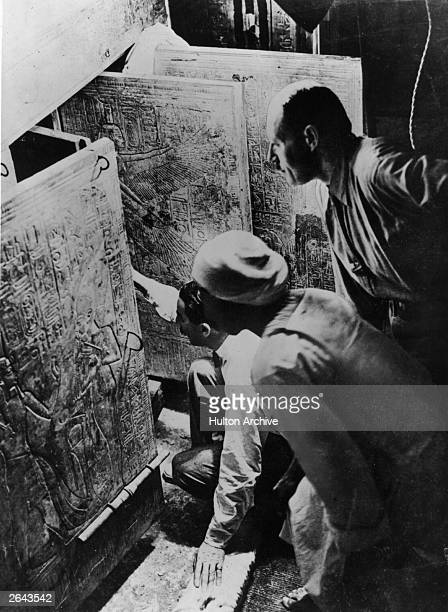 British archaeologist and Egyptologist Howard Carter and his assistant Arthur Callender opening the entrance to the fourth chamber of Tutankhamen's...