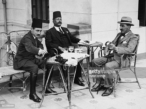 British archaeologist Howard Carter and two Egyptian officials sit on chairs at a table outside Egypt early 1920s