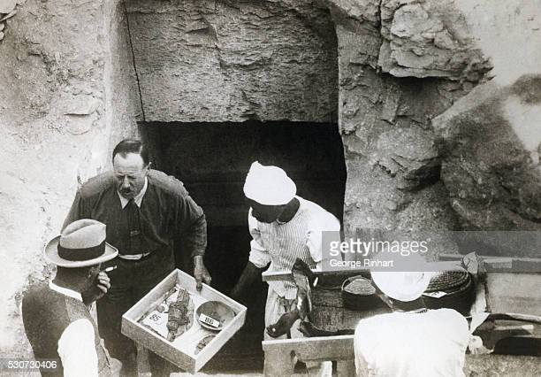 British archaeologist Howard Carter emerges from the tomb of the Egyptian Pharaoh Tutankhamun holding a box of archaeological artifacts Carter...