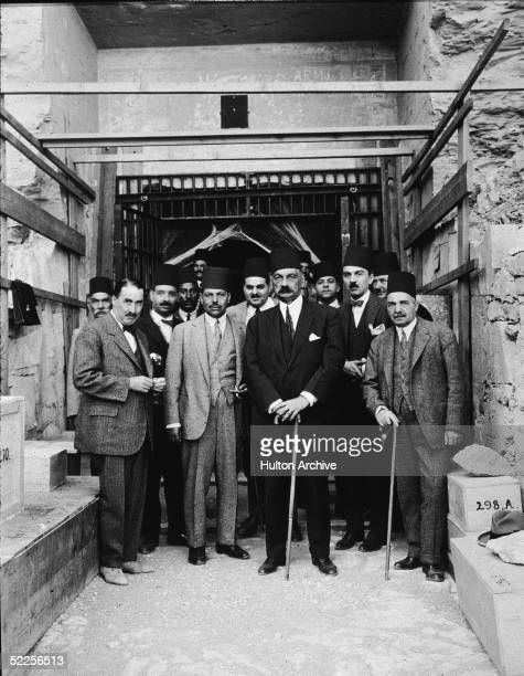 British archaeologist Howard Carter stands with Egyptian government officials at the entrance to the tomb of the Pharaoh Ramesses VI Valley of the...
