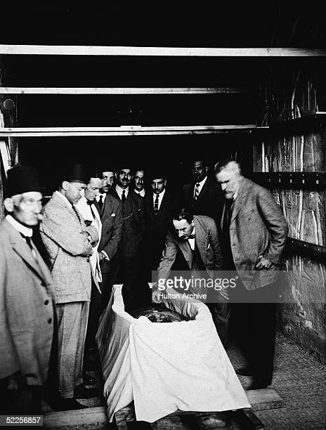British archaeologist Howard Carter with members of his team and Egyptian officials inspect the mummy of the Pharaoh Tutankhamen better known as King...