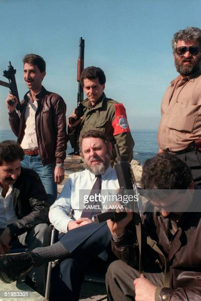 British Archbishop of Canterbury's Special Envoy Terry Waite relaxes 17 January 1987 on the Beirut seafront surrounded by heavily armed bodyguards...