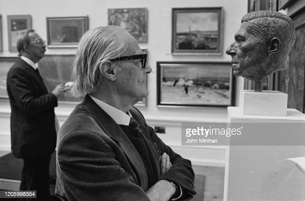 British architect, writer and broadcaster Sir Hugh Casson looking at the artworks on display at the Royal Academy's Summer Exhibition in London,...