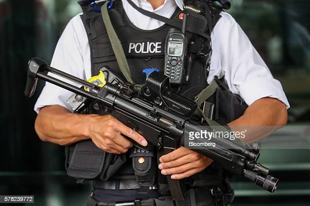 A British armed police officer stands guard outside Portcullis House parliamentary offices near to the Houses of Parliament in London UK on Wednesday...