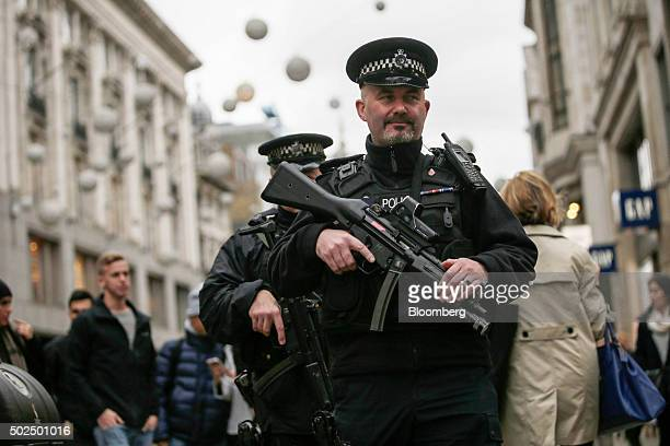 British armed police officers patrol on Oxford Street during the Boxing Day sales in London UK on Saturday Dec 26 2015 UK retail sales volumes...