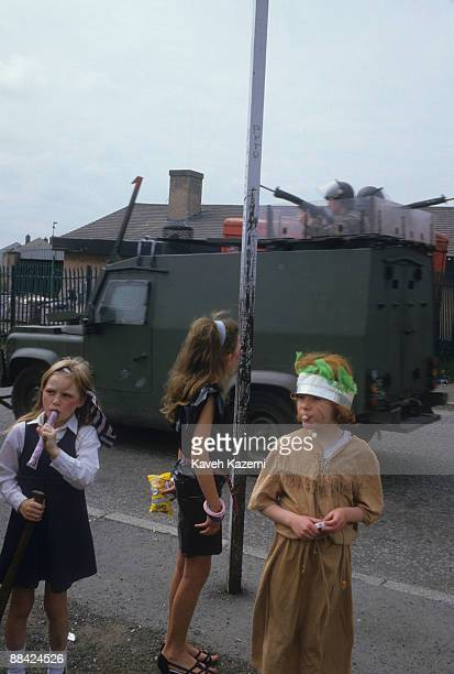 A British armoured vehicle on patrol passes three young girls coming from a children's fair in a Catholic area of west Belfast 18th September 1985