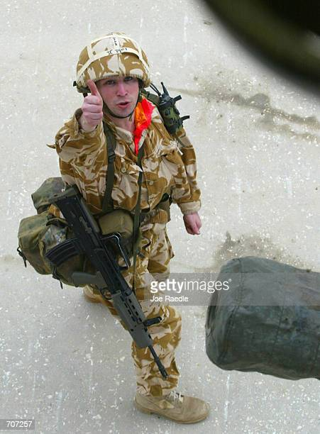 British Army 29 Commando Regiment of the Royal Artillery soldier gives the thumbs up after fixing a sling with a 105mm light gun to the chinook...