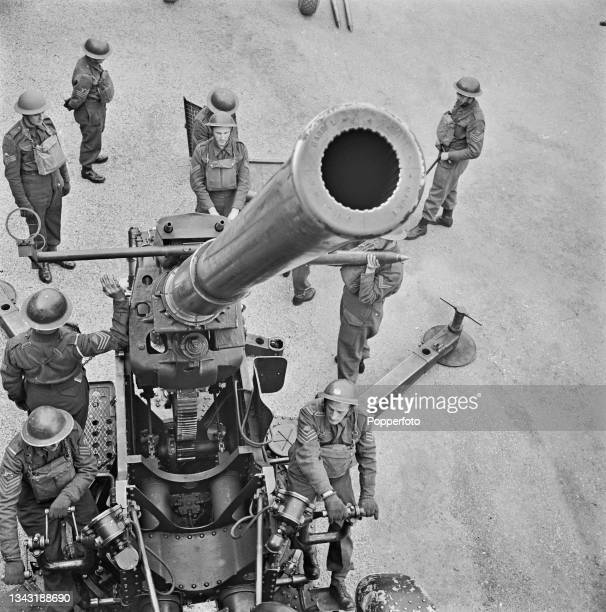 British Army anti-aircraft gun crew from the Royal Artillery prepare to fire their QF 3.7-inch AA gun at enemy aircraft from an artillery position in...