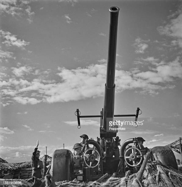 British Army anti-aircraft gun crew prepare to fire their QF 3.7-inch AA gun at enemy aircraft from an artillery position in southern England during...