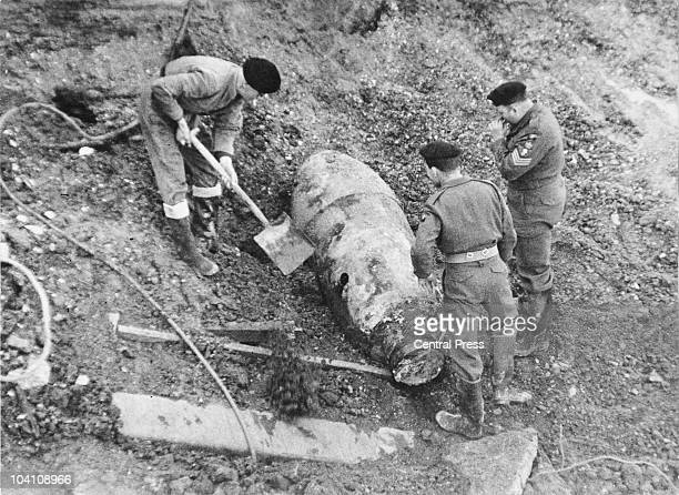 A British army bomb disposal squad digging round an unexploded 2000 pound German 'Hermann' bomb which was found on the Shell Building site on the...