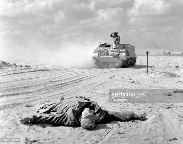 A British Army Bren Gun Carrier about to pass the body of a German Afrika Korps soldier lying by the side of the road in the wake of the decisive...