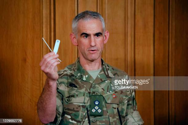 British Army Brigadier Joe Fossey, who is coordinating the mass coronavirus testing pilot in Liverpool, holds up the components of a lateral flow...