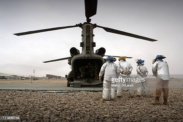 British Army fire fighters wait for a sign from the Royal Air Force Loadmaster inside the MERT CH-47 Chinook helicopter to approach it and carry out...