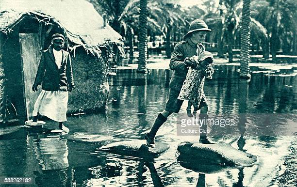 British Army in Mesopotamia during World War 1 soldier carrying a girl across flood water 1916 Modern day Iraq